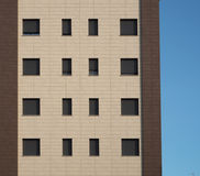 Facade with two brown shades of a residential building with gray shutters Stock Photo