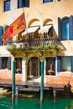 Facade of typical medieval house with flag on canal, Venice, Italy Stock Image