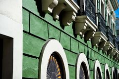 Facade wall on green plastered background in San Juan, Puerto Rico. House with windows and decorative balconies. Symmetry and urban geometry concept Royalty Free Stock Photos