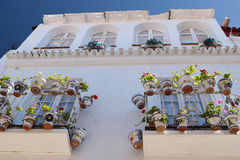 Facade of white buidings with flowers on  the balcony. Traditional house facade in Andalusia with balconies and flowers and ceramic pots Stock Photos