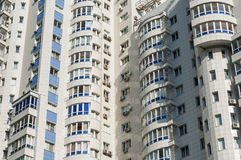 The facade of white high-rise apartment building. The facade of white high-rise residential building close-up Royalty Free Stock Photo