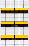 Facade with white tiles and yellow awnings Stock Image