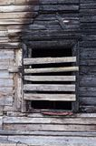 Facade window remains nailed with fresh planks on burnt wooden house Stock Photos