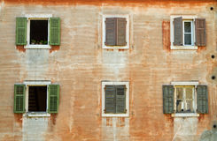 Facade with window-shutters. Old weathered european facade with wooden windows-shutters royalty free stock photography