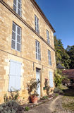 Facade with windows. And some pots, is located in aquitaine france. It is a vertical image on a sunny day Stock Image