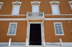 Facade, wooden door and symmetrical windows Stock Images