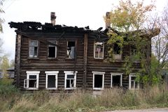 The facade of an wooden house damaged by a fire. The burnt section of the building. royalty free stock photo