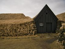 Facade of a wooden house surrounded by peat. The facade of a wooden house surrounded by peat in Keldur near Hella royalty free stock photos