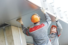Facade workers installing metal boarding. The Workers builders doing facade works with metal sheet boarding Stock Photography