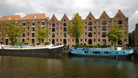 The facades of the houses and boats along the waterfront in Amsterdam.  Royalty Free Stock Images