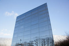 Facades of modern glass building with reflections of blue sky an Stock Photos
