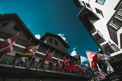 Facades with national flags in Olympic village. Wide-angle view from bottom of multiple national flags of different countries fixed to facades of wooden houses Stock Photos