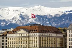 Facades Of Historic Buildings In The City Center Of Geneva, Switzerland On The Leman Lake With Snow Covered Alps Mountains Peaks Stock Photo