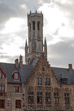 Facades of old buildings in Bruges, Belgium with Belfry tower in Royalty Free Stock Photos