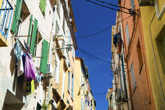 Facades of old colorful different houses in Perpignan, France. View on top of stone color buildings with windows with the drying linen stock photography