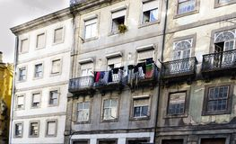 Facades of old houses in the center of the city with clothes hanging to dry, including a flag of Portugal, on the iron balconies i stock photo