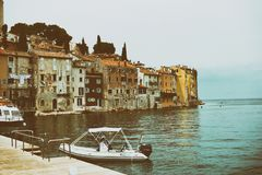 Facades with peeling plaster washed by the sea of the old town of Porec. Croatia and the boat in the foreground. Vintage toning.  royalty free stock image
