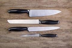 Facas de cozinha na placa de madeira Fotografia de Stock