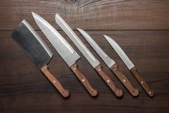 Facas de cozinha na tabela de madeira marrom Imagem de Stock