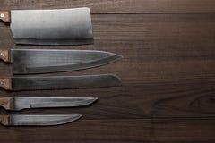 Facas de cozinha no fundo de madeira marrom Imagens de Stock Royalty Free