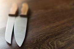 Facas de cozinha sentadas em um fundo de madeira Fotografia de Stock