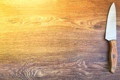 Facas de cozinha sentadas em um fundo de madeira Fotos de Stock Royalty Free