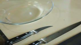 Facas do cozinheiro chefe ajustadas e salada deliciosa na placa que cozinha a demonstração no restaurante filme