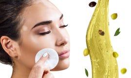 Faccia circolare la spruzzata di olio d'oliva vicino ai piedi femminili Concetto di Skincare fotografia stock