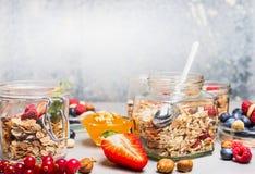 Faccia colazione in barattoli di vetro con i muesli, le bacche, i dadi ed i semi su fondo rustico leggero Immagini Stock Libere da Diritti
