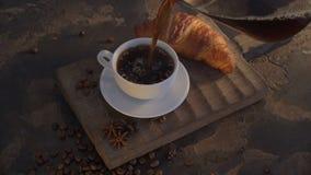 Faccia colazione con caffè ed i croissant sulla tavola d'annata di legno archivi video