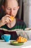 Faccia colazione con caffè ed il croissant con il giovane su fondo Immagine Stock Libera da Diritti