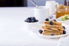 Faccia colazione con i crêpe, i mirtilli ed il caffè sottili dei pancake Immagine Stock