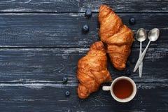 Faccia colazione con i croissant, i mirtilli ed il tè su una superficie rustica del blu Vista superiore, spazio per testo immagini stock