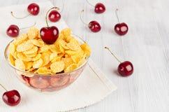 Faccia colazione con i fiocchi di mais dorati, ciliege mature sul bordo di legno bianco Fotografia Stock Libera da Diritti