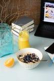 Faccia colazione con i muesli del mirtillo, succo d'arancia sulla tavola di vetro, i libri, computer portatile su fondo immagine stock libera da diritti