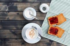 Faccia colazione con il latte e le fette biscottate del caffè con inceppamento fotografie stock