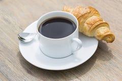 Faccia colazione con la tazza di caffè nero e del croissant Fotografie Stock Libere da Diritti