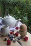 Faccia colazione con la teiera, la tazza, l'uovo e le bacche sulla tavola di legno Fotografia Stock Libera da Diritti