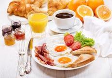 Faccia colazione con le uova fritte, i croissant, il succo, il caffè ed i frutti fotografia stock