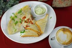 Faccia colazione con le uova rimescolate, con il pomodoro, il caffè ed il pane tostato Fotografia Stock