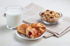 Faccia colazione con un croissant, i muesli e un bicchiere di latte Fotografia Stock Libera da Diritti