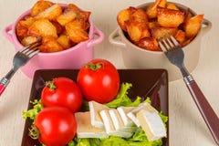 Faccia colazione da formaggio, i pomodori, patate e da ogni parte di insalata su una tavola di legno Fotografia Stock Libera da Diritti