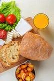 Faccia colazione da pane, il formaggio, i pomodori, patate e da ogni parte di insalata su una tavola di legno Fotografia Stock