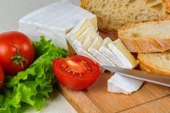 Faccia colazione da pane, il formaggio, pomodori e da ogni parte di insalata su una tavola di legno Fotografie Stock Libere da Diritti