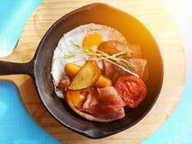 Faccia colazione nella cottura della pentola con le uova fritte, le salsiccie, bacon Immagine Stock