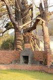 Faccia fuoco il posto contro la vecchia casa dell'azienda agricola con gli alberi Fotografia Stock