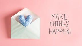 Faccia le cose accadere messaggio con un cuscino blu del cuore Fotografie Stock