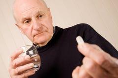 Faccia maturare il ridurre in pani o la pillola della holding dell'uomo più anziano con acqua Fotografia Stock Libera da Diritti