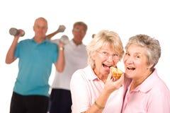 Faccia maturare le signore che mangiano la torta immagini stock