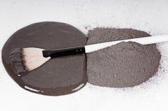 Faccia scorrere dalla polvere vulcanica nera dell'argilla per le procedure cosmetiche fotografie stock libere da diritti